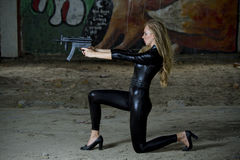 Gun woman in leather catsuit. Shooting from machine gun stock photography