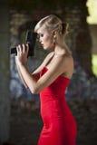 Gun woman in red dress. In vintage look posing in old fabric ruins royalty free stock image