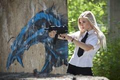 Gun woman. Young gun woman holding a automatic gun playing a spy outdoor stock image