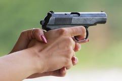 Gun in women's hands Royalty Free Stock Photo
