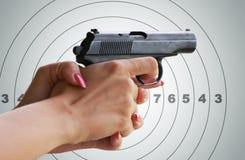 Gun in women's hands. Royalty Free Stock Photos