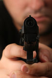 Gun you down. Shallow depth of field shot of a man jolding a semiautomatic handgun, focus on barrel Stock Images