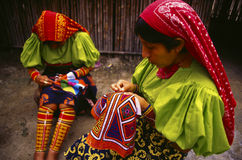 Guna women sewing mola designs. PANAMA Tupile -- Guna Indian women embroider the famous Guna 'Molas' - geometric designs worn by many Guna women. Molas are a Royalty Free Stock Images