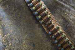 Gunbelt用在破旧的皮革背景的子弹 免版税库存图片