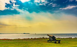 The guner at side the ocean. The ocean has battleship in the cloud day and The guner on the shore Stock Photo