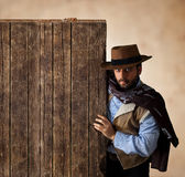 Gunfighter near wooden blank table. Stock Photography
