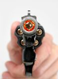 Gunfire. Gun being fired with bullet exploding out toward viewer Stock Image