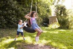 Gunga för broderPushing Sister On gummihjul i trädgård royaltyfri fotografi