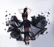 Gunga. Kvinna i fladdraklänning med fjärilar Arkivfoto