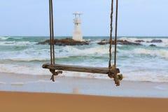 Gunga och fyr på stranden arkivfoton