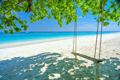 Gunga på den vita stranden med det blåa havet och blå himmel Fotografering för Bildbyråer
