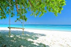 Gunga på den vita stranden med det blåa havet och blå himmel Royaltyfri Foto