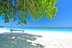 Gunga på den vita stranden med det blåa havet och blå himmel Arkivfoton