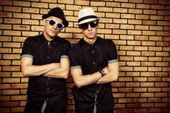 Gungsters. Two handsome men in black shirts and black sunglasses against brick wall royalty free stock image