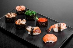 Gunkan και σούσια που τίθενται με το σολομό, το χέλι, τις γαρίδες, το chukka και το κοτόπουλο σε ένα μαύρο πιάτο σε ένα σκοτεινό  στοκ φωτογραφία με δικαίωμα ελεύθερης χρήσης