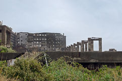 Gunkanjima with light fog. Gunkanjima, or Hashima, is an abandoned islet near Nagasaki city completely covered in industrial ruins. Once a coal mine run by Royalty Free Stock Photo