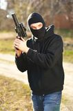 Gunman. In black mask holding gun with silencer stock photos