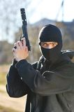 Gunman. In black mask holding gun with silencer royalty free stock images