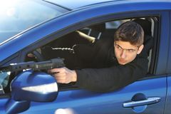 Gunman. In car holding gun with silencer stock images