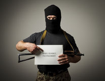 Gunman is holding white paper. False witness. Man in mask with gun is holding white paper. Peacemaker or false concept royalty free stock images