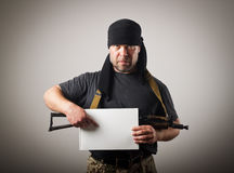 Gunman is holding white paper. Man in mask with gun is holding white paper stock images