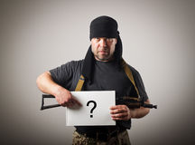 Gunman is holding white paper with question-mark. Stock Photo