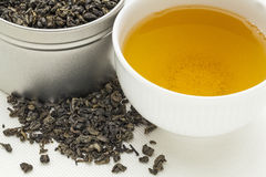 Gunpowder green tea. A white cup of drink and loose leaves on canvas stock photo