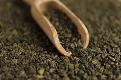 Gunpowder green tea in scoop. On tea background. Selective focus stock photo