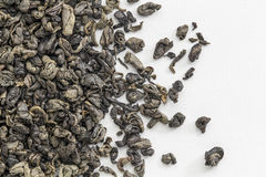 Gunpowdert green tea. Background texture of loose leaf Chinese gunpowder (pearl) green tea spilled over white artist canvas Royalty Free Stock Image