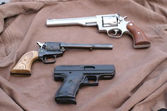 Guns. Collection of pistols against a brown back drop stock images