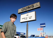 Guns and Ammo. Boy in front of seedy guns/ammo/pawn area Stock Photo