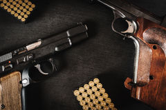 Guns and bullets on the table. Black pistols and bullets on a black wooden table Stock Photography