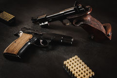 Guns and bullets on the table. Black pistols and bullets on a black wooden table Stock Image