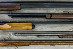 Guns hanging on rustic wooden wall Royalty Free Stock Images