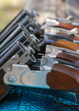 Guns in Line. A row of guns used for clay pigeon shooting resting over a fence. Guns are in the safe, broken position Stock Photography