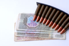 Guns and Money. Russian Money and Clip of Russian SKS Bullets Stock Photo