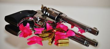 Guns & Roses. Ruger 45 Pistol with red rose petals and ammunition scattered around it Stock Photography