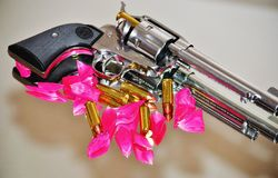 Guns & Roses. Ruger 45 Pistol with red rose petals and ammunition scattered around it Stock Images