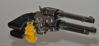 Guns & Roses. Ruger 45 Pistol with a yellow rose Royalty Free Stock Photography