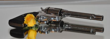 Guns & Roses. Ruger 45 Pistol with a yellow rose Royalty Free Stock Image