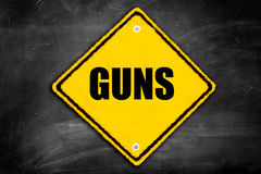 Guns written on caution sign. On a black chalkboard with room for print Stock Photo