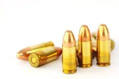 Gunshot. Live 9mm pistol round against white Stock Image