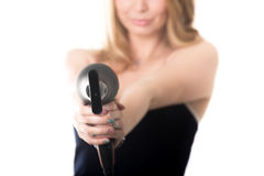 Gunshot from hairdryer. Young funny attractive blond Caucasian woman fooling around, holding black hair dryer like gun aiming towards camera, close up, focus on Royalty Free Stock Photo