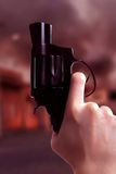 Gunshot scene. Gun over apocalyptic background - processed colors Stock Image