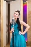 Gunstmeisje die met rode lippen een microfoon houden Stock Foto's