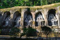 Gunung Kawi寺庙复合体被雕刻入与密林的石峭壁峭壁的在巴厘岛,印度尼西亚 免版税库存照片