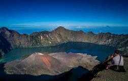 Gunung Rinjani from above. Tourist sitting on the rim of the crater of Gunung Rinjani volcano in Lombok island,  Indonesia Royalty Free Stock Photography