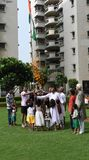 Gurgaon Indien: Augusti 15th, 2015: Folk i ett lokalt samhälle i Gurgaon, Delhi som lyfter flaggan på självständighetsdagen Royaltyfri Fotografi