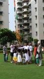 Gurgaon, la India: 15 de agosto de 2015: Gente en una sociedad local en Gurgaon, Delhi que aumenta la bandera el Día de la Indepe Fotografía de archivo libre de regalías
