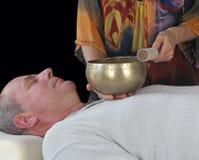 Guérisseur sain travaillant avec la cuvette tibétaine de chant Images stock